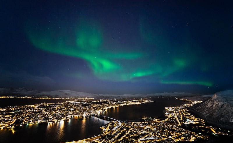 norway tromso northern lights behind city lights