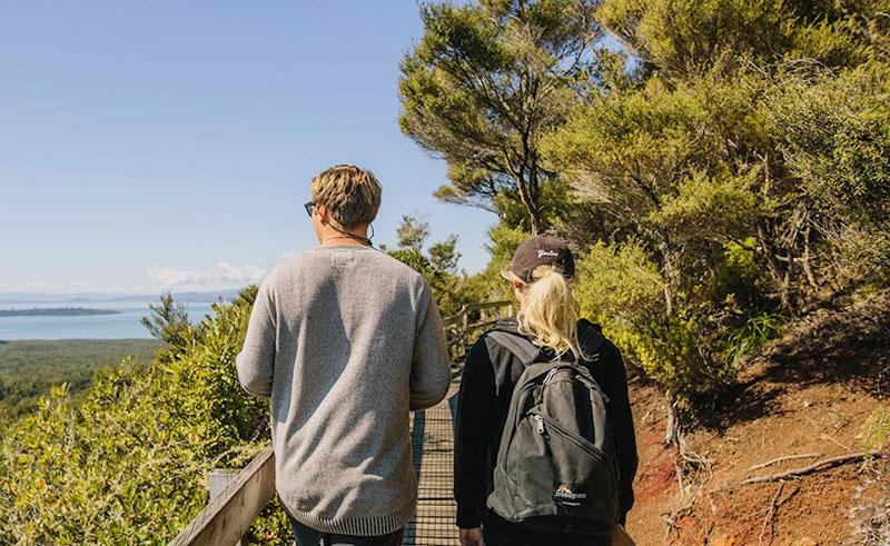 rangitoto volcanic island tour couple walking up broadwalk to volcano top