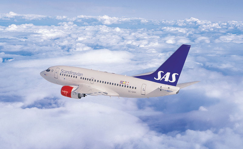 sweden sas aircraft in flight above clouds