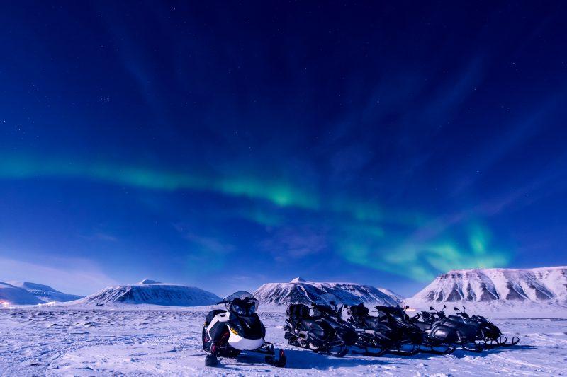 svalbard aurora over snowmobiles longyearbyen istk