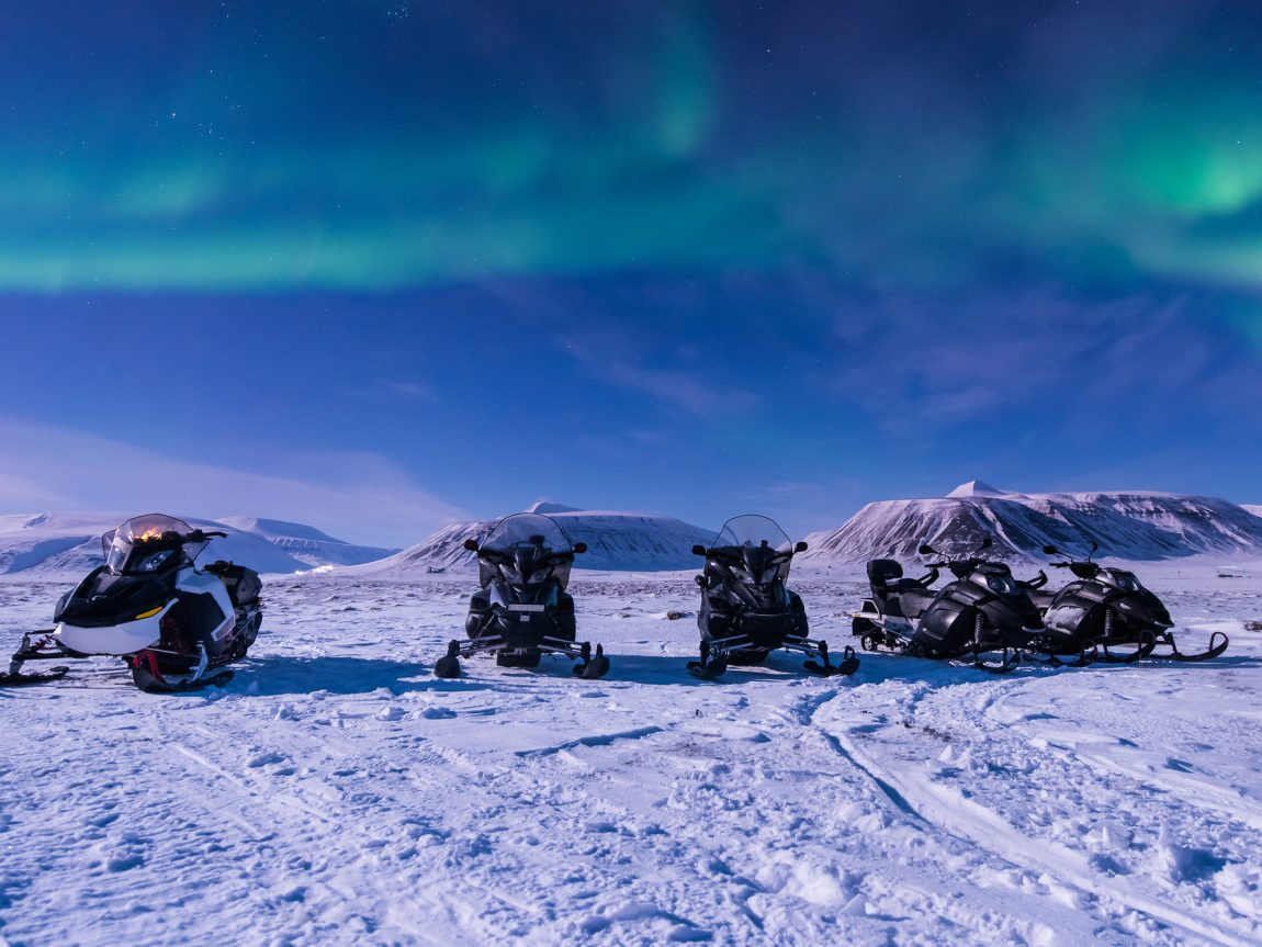 svalbard longyearbyen snowmobiles with aurora istk