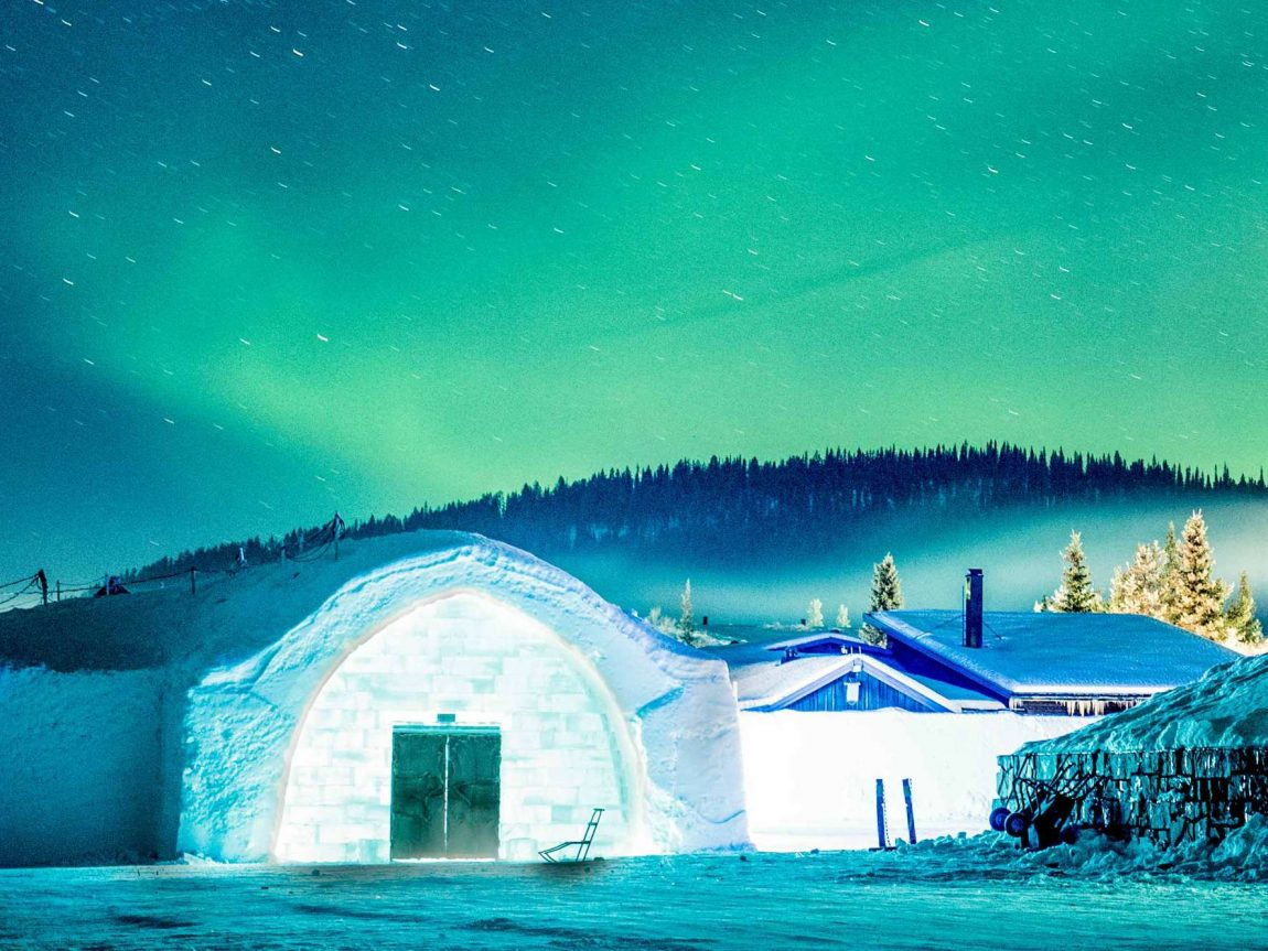 swedish lapland icehotel entrance with aurora overhead ak