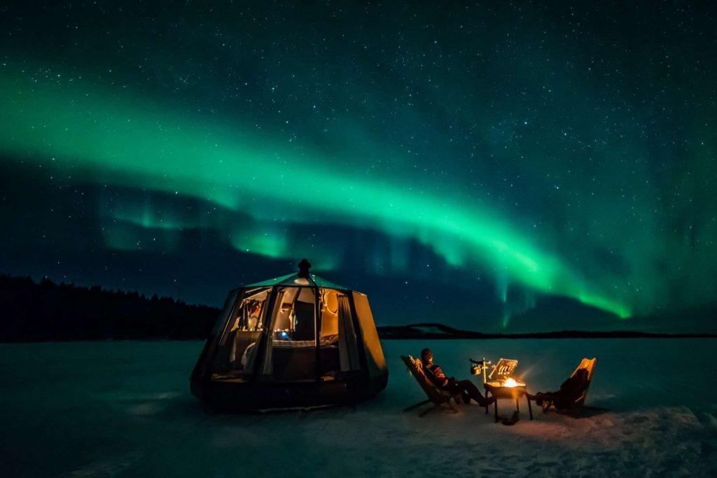 inari wilderness hotel aurora hut with northern lights above