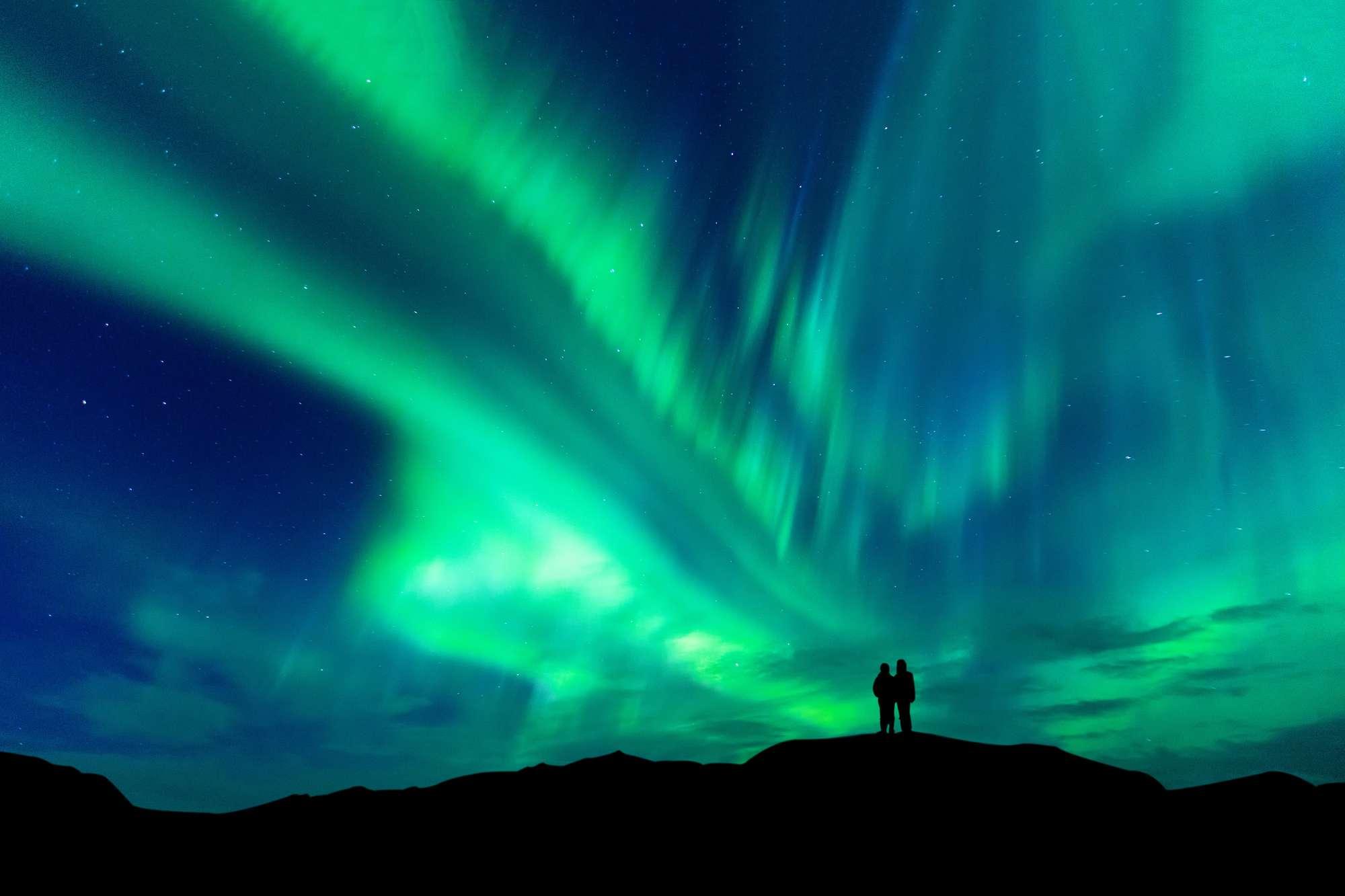 swedish lapland couple watching aurora borealis istk