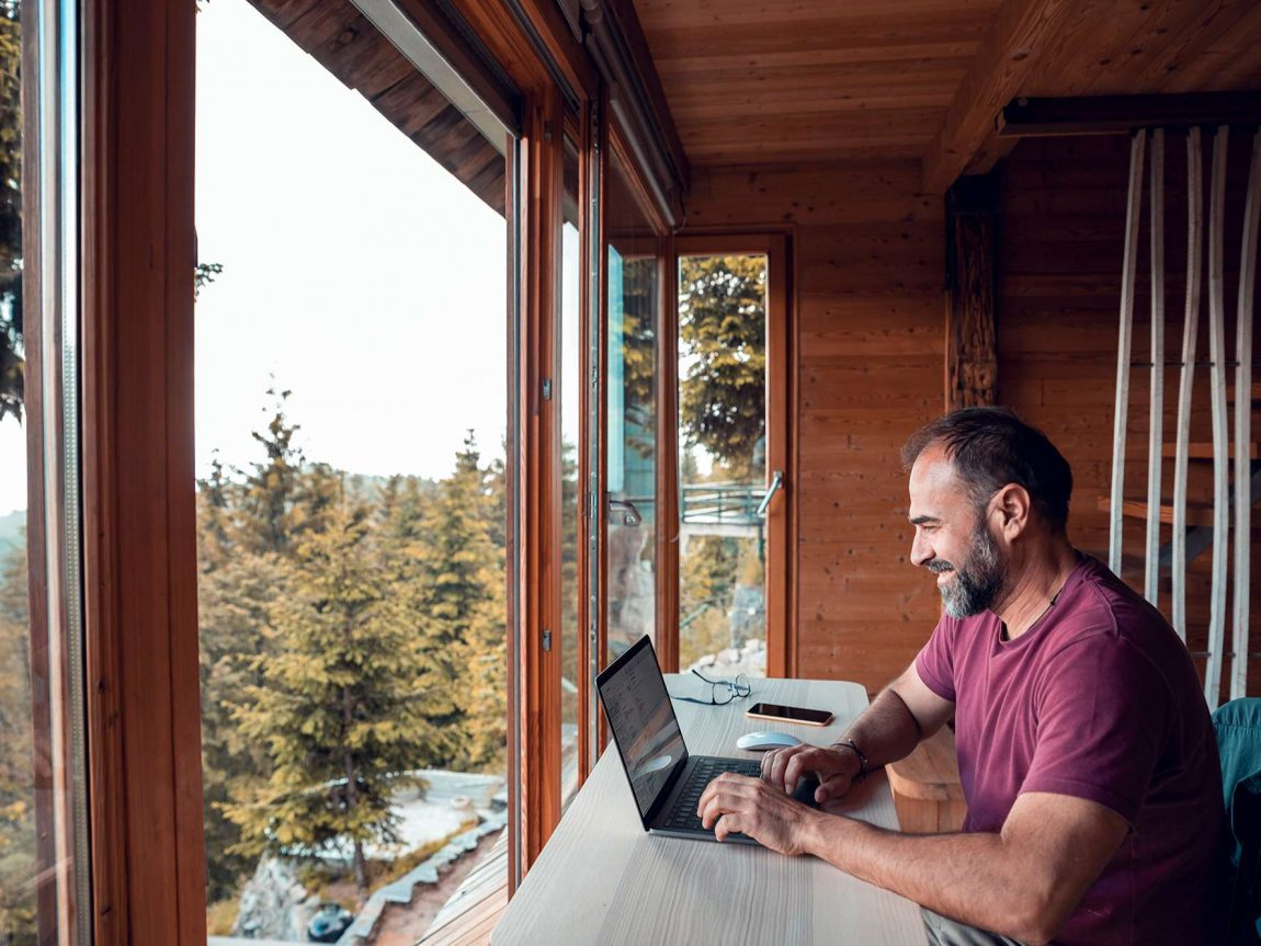 remote working man with laptop overlooking view istk