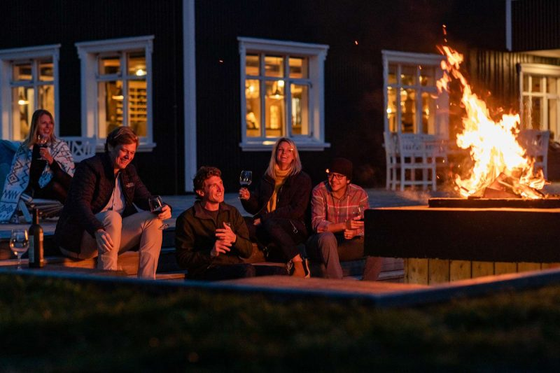 iceland skalakot country manor group around outdoor firepit